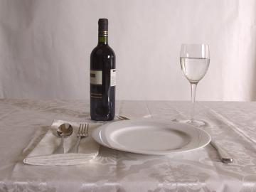 сервированный к обеду стол с бутылкой столового красного вина